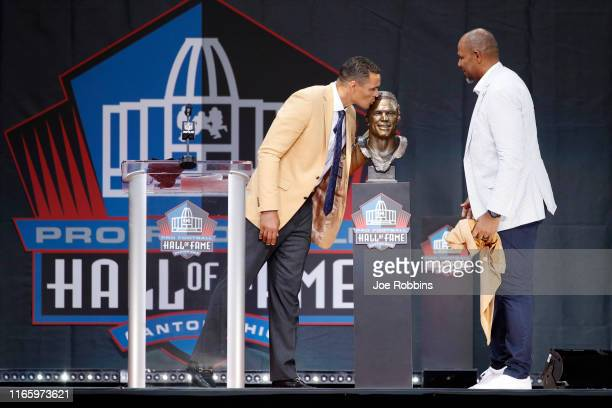 Tony Gonzalez kisses his bust as his presenter Dennis Allen looks on during his enshrinement into the Pro Football Hall of Fame at Tom Benson Hall Of...