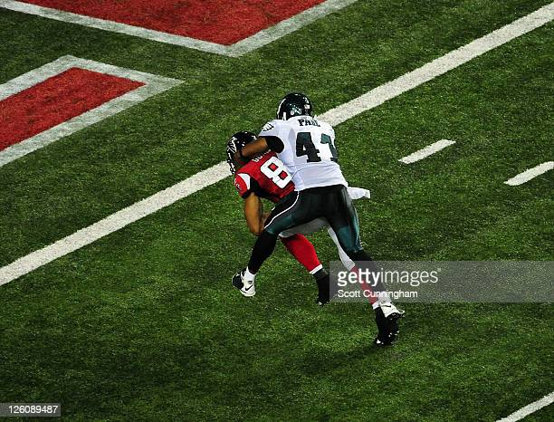 Tony Gonzalez of the Atlanta Falcons carries Jarrad Page against the Philadelphia Eagles for a touchdown at the Georgia Dome on September 18 2011 in...