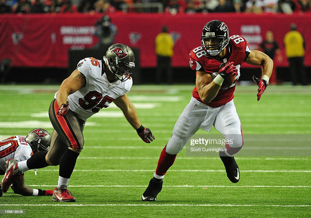 Tony Gonzalez #88 of the Atlanta Falcons runs with a catch against Gary Gibson #95 of the Tampa Bay Buccaneers at the Georgia Dome on December 30, 2012 in Atlanta, Georgia