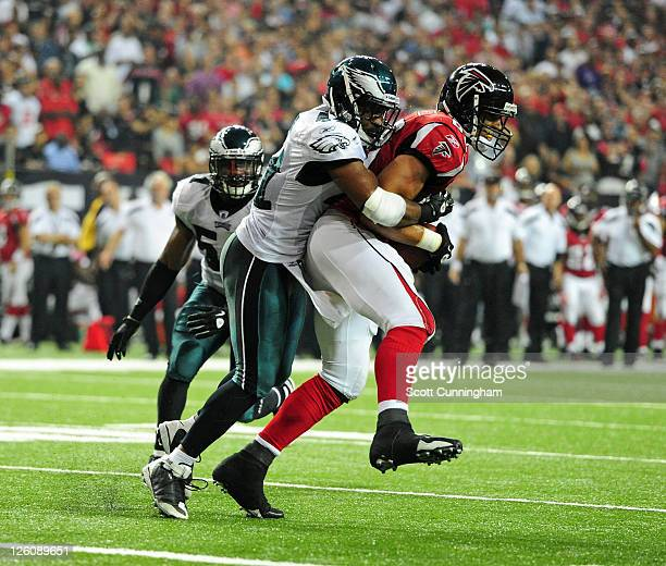 Tony Gonzalez of the Atlanta Falcons runs with a catch against Jarrad Page of the Philadelphia Eagles at the Georgia Dome on September 18 2011 in...