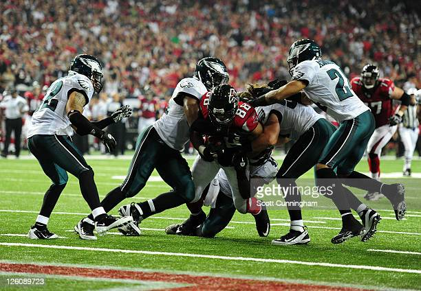 Tony Gonzalez of the Atlanta Falcons runs with a catch against Jarrad Page and Nnamdi Asomhuga of the Philadelphia Eagles at the Georgia Dome on...