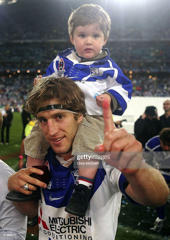 Tony Grimaldi of the Bulldogs celebrates with his son after defeating the Roosters during the NRL Grand Final between the Sydney Roosters and the Bulldogs held at Telstra Stadium, October 3, 2004 in Sydney, Australia.