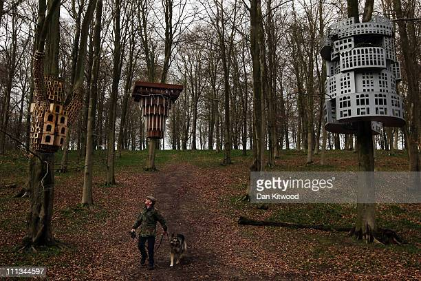 Tony Hall walks with his dog through an installation entitled 'Super Kingdom' which hangs in trees in King's Wood as part of the Stour Valley Arts...