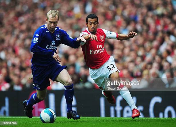Tony Hibbert of Everton and Theo Walcott of Arsenal challenge for the ball during the Barclays Premier League match between Arsenal and Everton at...