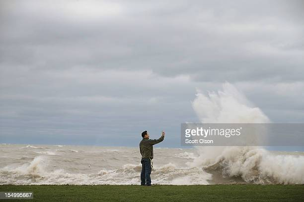 Tony Inclan trys to photograph himself while waves generated from the remnants Hurricane Sandy crash into the shoreline of Lake Michigan on October...