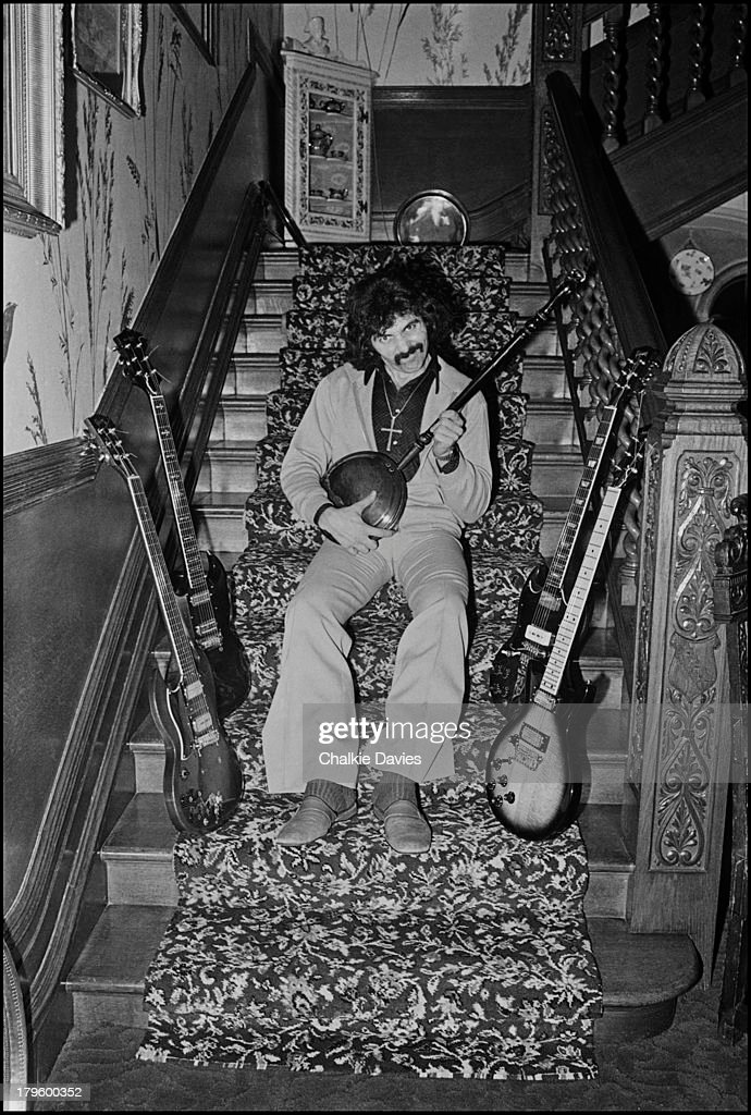Tony Iommi, guitarist with Black Sabbath, poses with a selection of his guitars, playing a bedpan, at his manor house home in Staffordshire, UK, 1975.