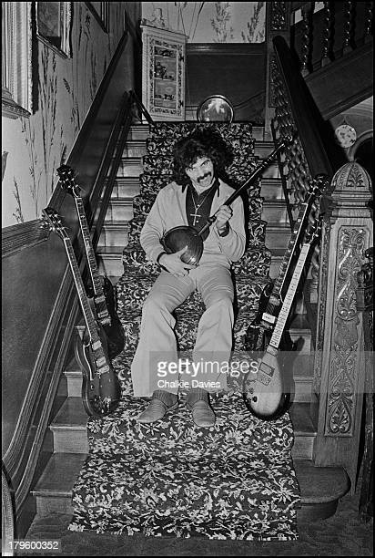 Tony Iommi guitarist with Black Sabbath poses with a selection of his guitars playing a bedpan at his manor house home in Staffordshire UK 1975
