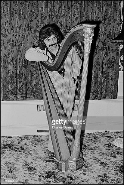 Tony Iommi guitarist with Black Sabbath poses with an antique concert harp at his manor house home in Staffordshire UK 1975