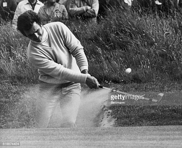 Tony Jacklin of Britain raises the dust as he blasts out of a bunker by the 15th green during the third round of the British Open Golf Championship...