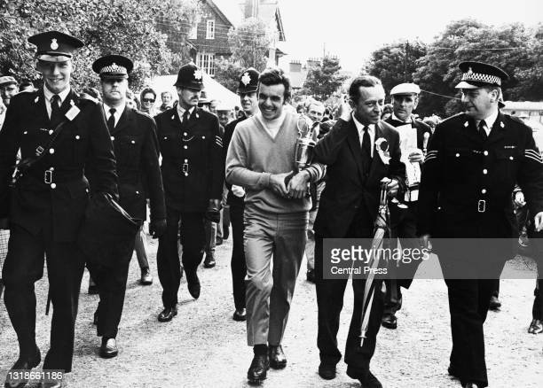 Tony Jacklin of Great Britain walks back to the clubhouse holding the Champion Golfer Claret Jug trophy with a police escort after winning the 98th...