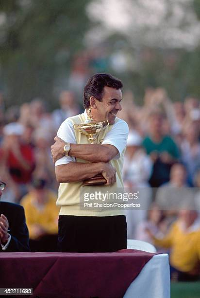 Tony Jacklin the nonplaying captain of the European team hugs the trophy after retaining it despite drawing the Ryder Cup golf competition held at...