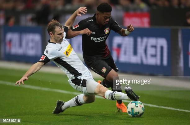 Tony Jantschke of Moenchengladbach and Leon Bailey of Leverkusen battle for the ball during the Bundesliga match between Bayer 04 Leverkusen and...