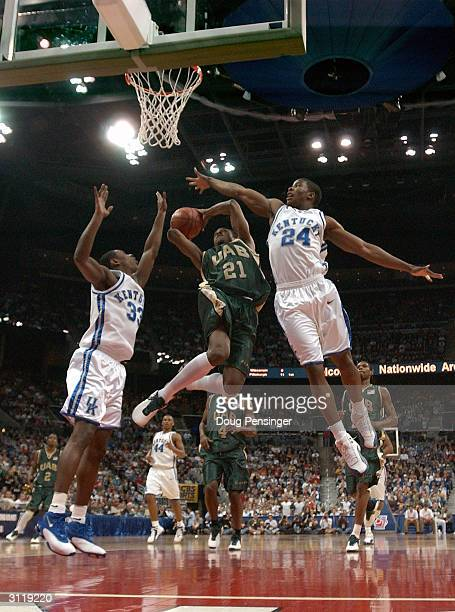 Tony Johnson of the UAB Blazers drives for a shot attempt between Antwain Barbour and Kelenna Azubuike of the Kentucky Wildcats as the Blazers upset...