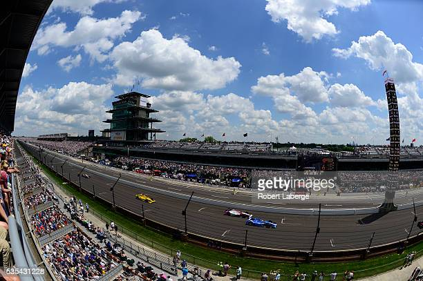 Tony Kanaan of Brazil driver of the Chip Ganassi Racing Chevrolet leads a pack of cars during the 100th running of the Indianapolis 500 mile race at...