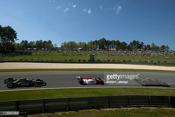 Tony Kanaan of Brazil driver of the KV Racing Technology Lotus Dallara Honda leads Vitor Meira and E J Viso during the IndyCar Series Honda Indy...