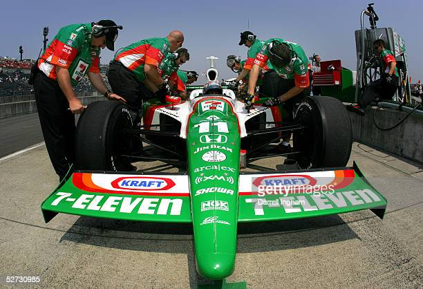 Tony Kanaan sits aboard the Andretti Green Racing Team 7Eleven Dallara Honda while his mechanics work during qualifying for the Indy Racing League...