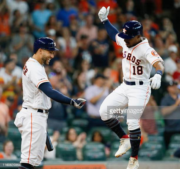 Tony Kemp of the Houston Astros celebrates with George Springer after hitting a two-run home run in the second inning against the Los Angeles Angels...