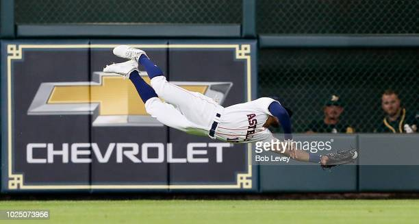 Tony Kemp of the Houston Astros makes a diving attempt on a line drive hit by Jed Lowrie of the Oakland Athletics but is unable to hold onto the ball...