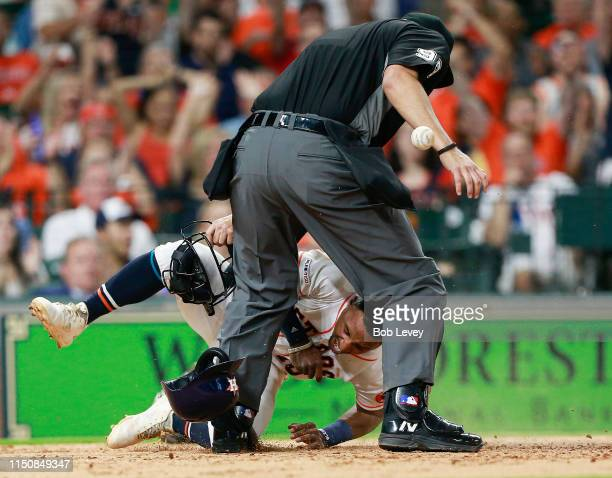 Tony Kemp of the Houston Astros scores on a wild pitch in the fifth inning as he gets tangled up with home plate umpire Mark Ripperger at Minute Maid...