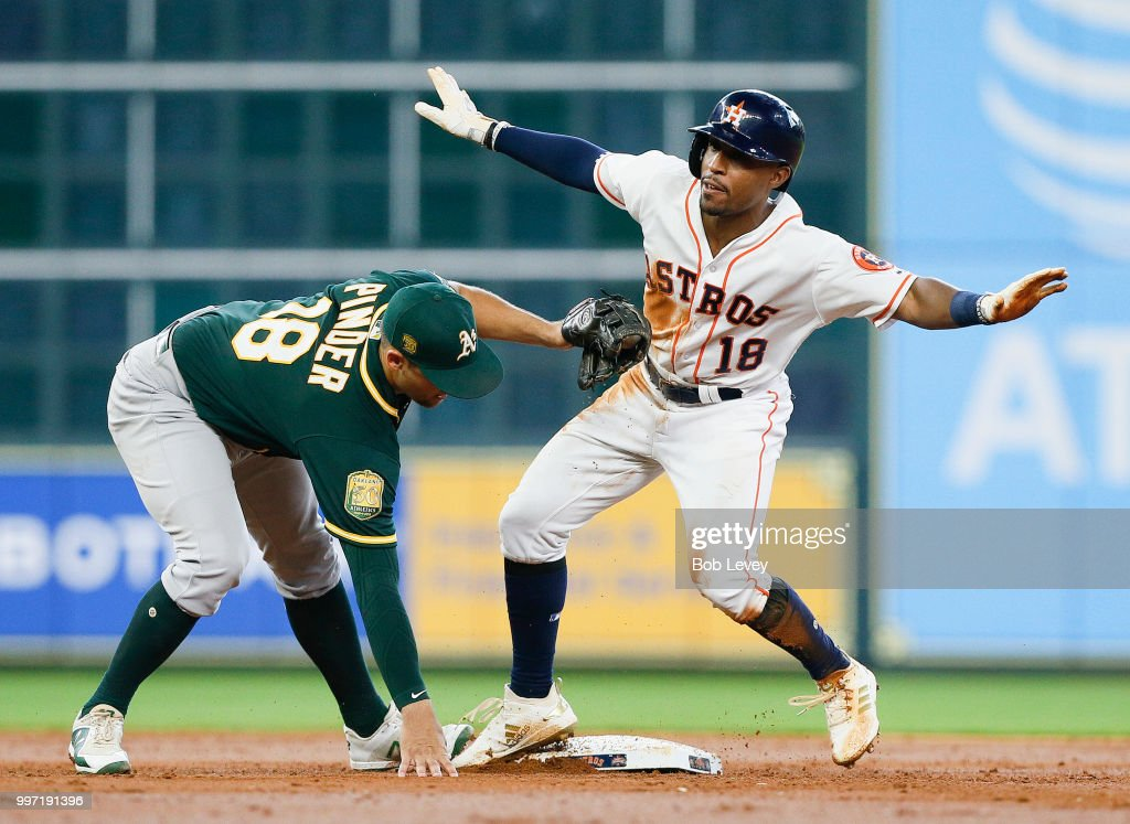 Tony Kemp #18 of the Houston Astros steals second base in the third inning as Chad Pinder #18 of the Oakland Athletics applies the tag at Minute Maid Park on July 12, 2018 in Houston, Texas.