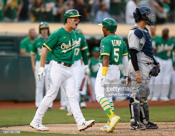 Tony Kemp of the Oakland Athletics celebrates with Mark Canha after hitting a two-run home run in the bottom of the eighth inning against the New...
