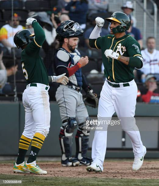 Tony Kemp of the Oakland Athletics congratulates teammate Edwin Diaz as he crosses home plate after hitting a two-run home run in the eighth inning...