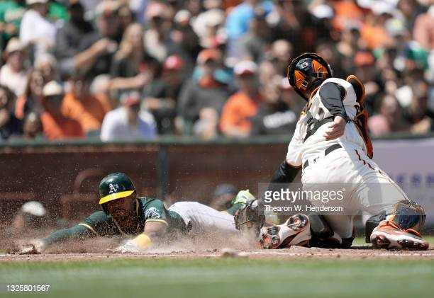Tony Kemp of the Oakland Athletics slides past the tag of Buster Posey of the San Francisco Giants to score in the top of the sixth inning at Oracle...