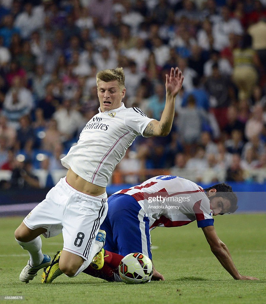 Tony Kroos (8) of Real Madrid vies for the ball with Raul Garcia (R) of Atletico Madrid during the Spanish La Liga soccer match between Real Madrid and Atletico Madrid at the Santiago Bernabeu stadium in Madrid, Spain on September 13, 2014.