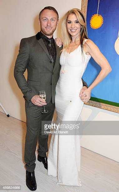 """Tony Lewis and Stasha Palos attend a private view of """"And The Stars Shine Down"""" by Stasha Palos at the Saatchi Gallery on December 2, 2014 in London,..."""