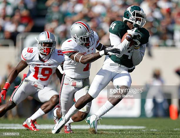Tony Lippett of the Michigan State Spartans makes a second quarter catch in front of Travis Howard of the Ohio State Buckeyes at Spartan Stadium on...