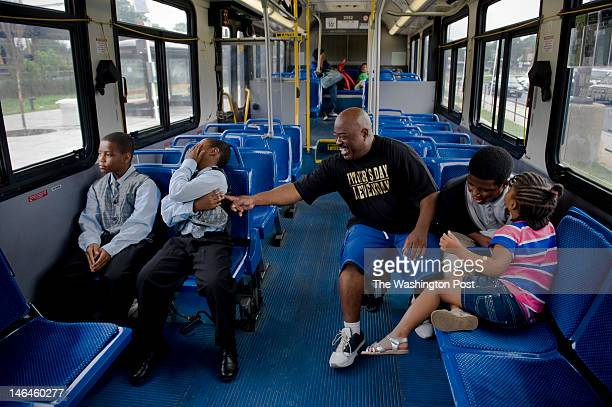 Tony Loring jokes with one of his twin sons Tyrus on a Metro bus en route to the twins' promotion ceremony from Kenilworth Elementary School on...
