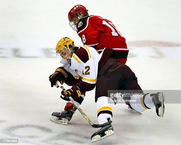 Tony Lucia of the Minnesota Gophers is checked by Dan Peace of the RPI Engineers October 12, 2007 at the Xcel Energy Center in St. Paul, Minnesota.
