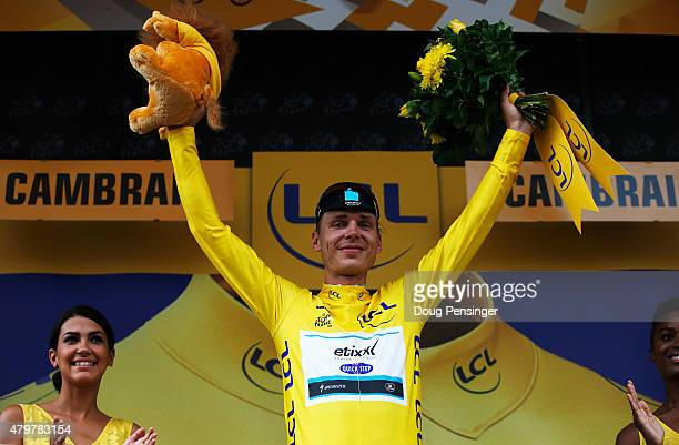 Tony Martin of Germany and EtixxQuick Step celebrates as he is awarded the yellow jersey on the podium after stage four of the 2015 Tour de France a...