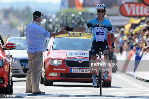 Tony Martin of Germany riding for Omega Pharma-Quick Step is greeted by Event Director Jean-Francois Pescheux as he crosses the finish line after his...