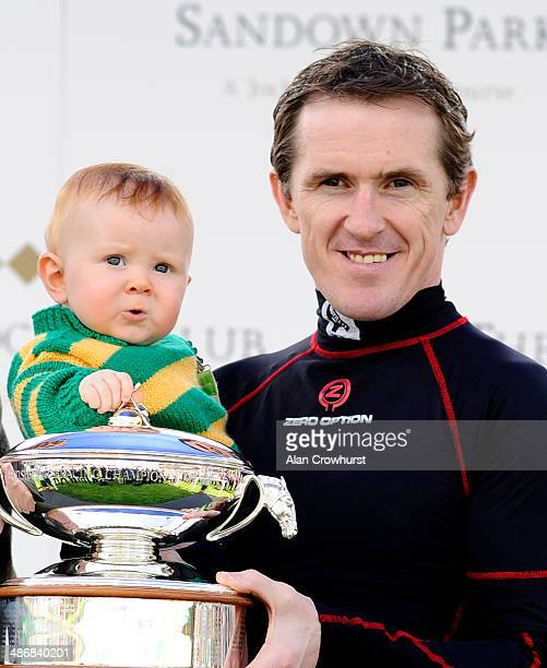 Tony McCoy and his son Archie pose with his trophy for being champion jockey at Sandown racecourse on April 26 2014 in Esher England