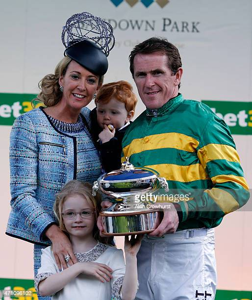 Tony McCoy holds the champion jockeys trophy with wife Chanelle and children Eve and Archie at Sandown racecourse on April 25 2015 in Esher England