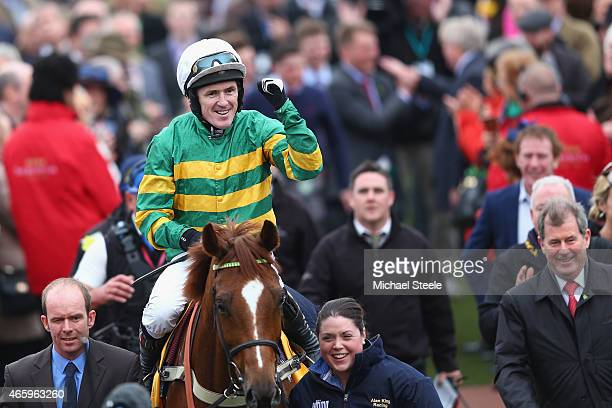 Tony McCoy on Uxizandre celebrates with owner JP McManus after victory in the Ryanair Steeplechase during day three of the Cheltenham Festival at...