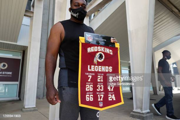Tony McGhee of Baton Rouge, Louisiana, poses with the banner he purchased at the Fan Store at FedEx Field, home of the NFL's Washington Redskins...
