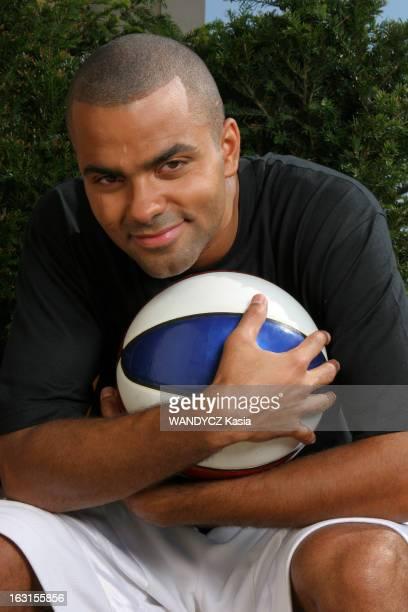 Tony Parker In Paris. Attitude souriante de Tony PARKER serrant contre lui un ballon de basket, assis sur le balcon de sa chambre de l'hôtel Park...