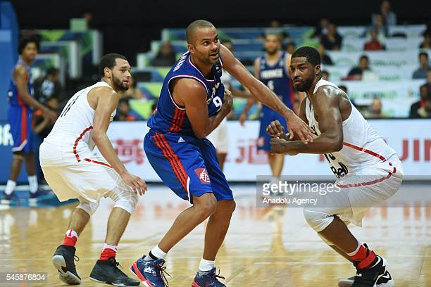 Tony Parker of France attempts to escape his defenders Tyler Ennis and Tristan Thompson of Canada during their match for the FIBA 2016 Olympic...