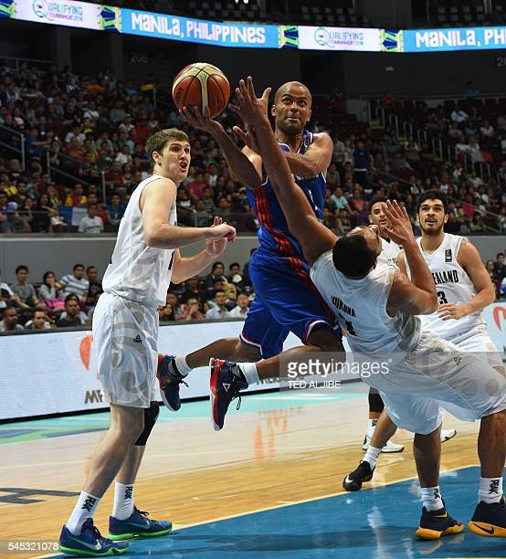 Tony Parker of France laysup against Mika Vukona of New Zealand during their 2016 FIBA Olympic men's qualifying basketball tournament in Manila on...
