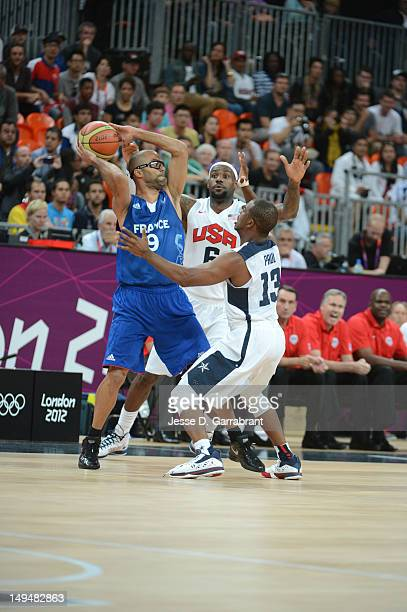 Tony Parker of France passes against LeBron James and Chris Paul of the USA Mens Senior National team at the Olympic Park Basketball Arena during the...