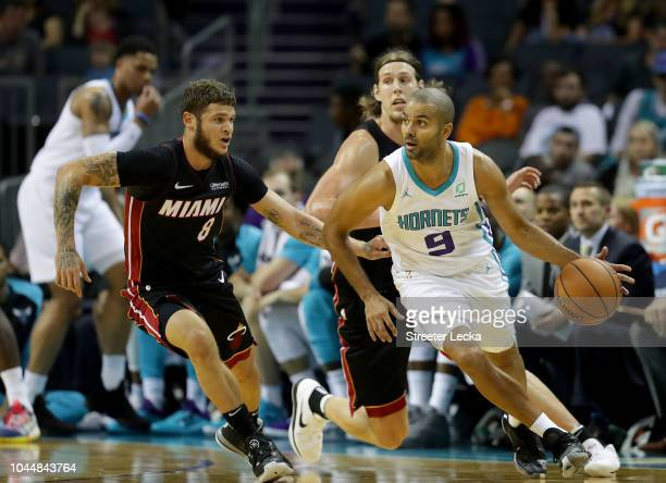 Tony Parker of the Charlotte Hornets looks to pass against Tyler Johnson of the Miami Heat during their game at Spectrum Center on October 2 2018 in...