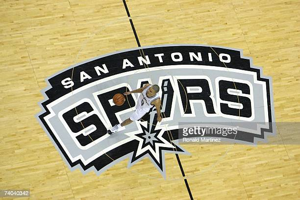 Tony Parker of the San Antonio Spurs dribbles upcourt over the center court logo against the Denver Nuggets in Game Two of the Western Conference...