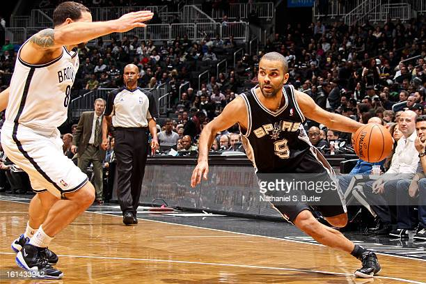 Tony Parker of the San Antonio Spurs drives against Deron Williams of the Brooklyn Nets on February 10 2013 at the Barclays Center in the Brooklyn...
