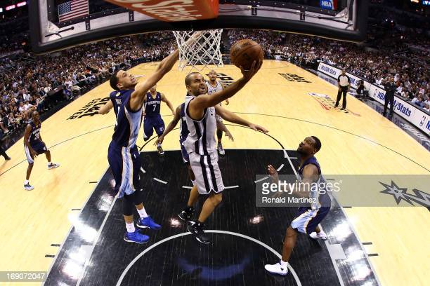 Tony Parker of the San Antonio Spurs drives for a shot attempt against Austin Daye and Tony Allen of the Memphis Grizzlies during Game One of the...