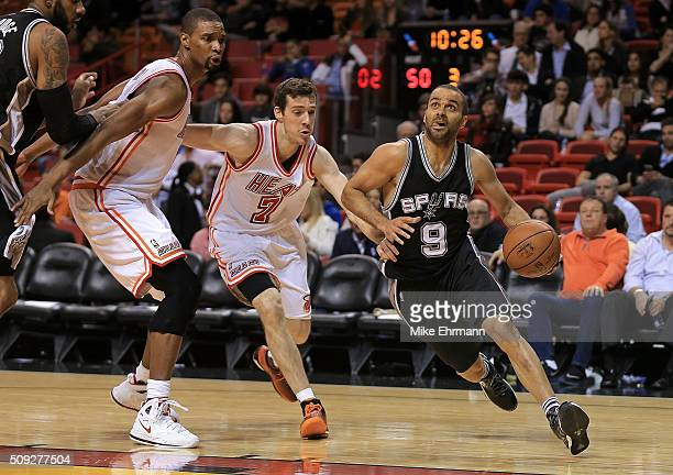 Tony Parker of the San Antonio Spurs drives past Goran Dragic and Chris Bosh of the Miami Heat during a game at American Airlines Arena on February 9...