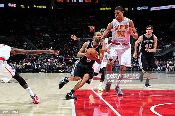 Tony Parker of the San Antonio Spurs drives to the basket against Walter Tavares of the Atlanta Hawks on October 14 2015 at Philips Arena in Atlanta...