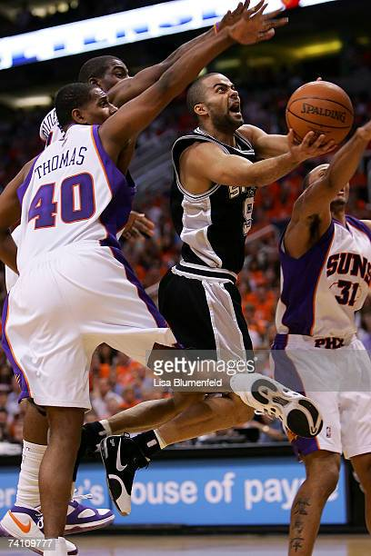 Tony Parker of the San Antonio Spurs goes up for a layup as Amare Stoudemire and Kurt Thomas of the Phoenix Suns look to block the shot from behind...