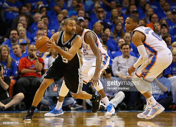 Tony Parker of the San Antonio Spurs handles the ball against Kevin Durant and Russell Westbrook of the Oklahoma City Thunder in the third quarter...